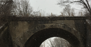 Old stone bridge in a light snow